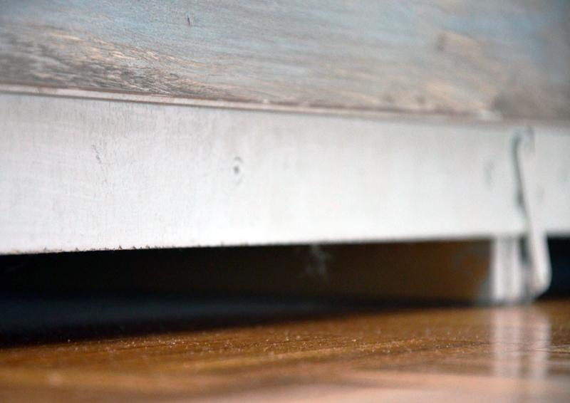 dettaglio della parte inferiore della testiera che riveste le due cassettiere